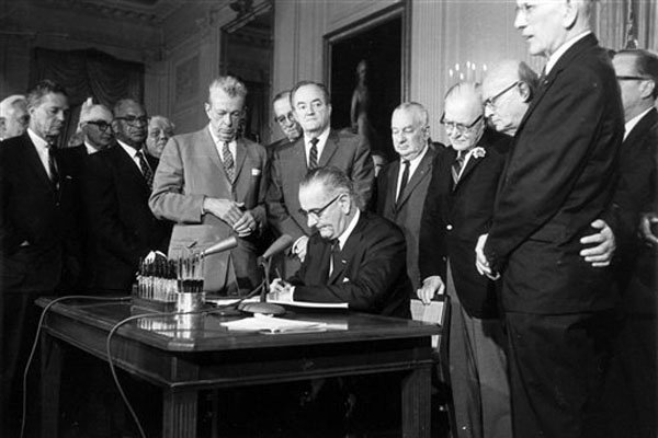 Lyndon Johnson signing equal right act based on gender. Image source